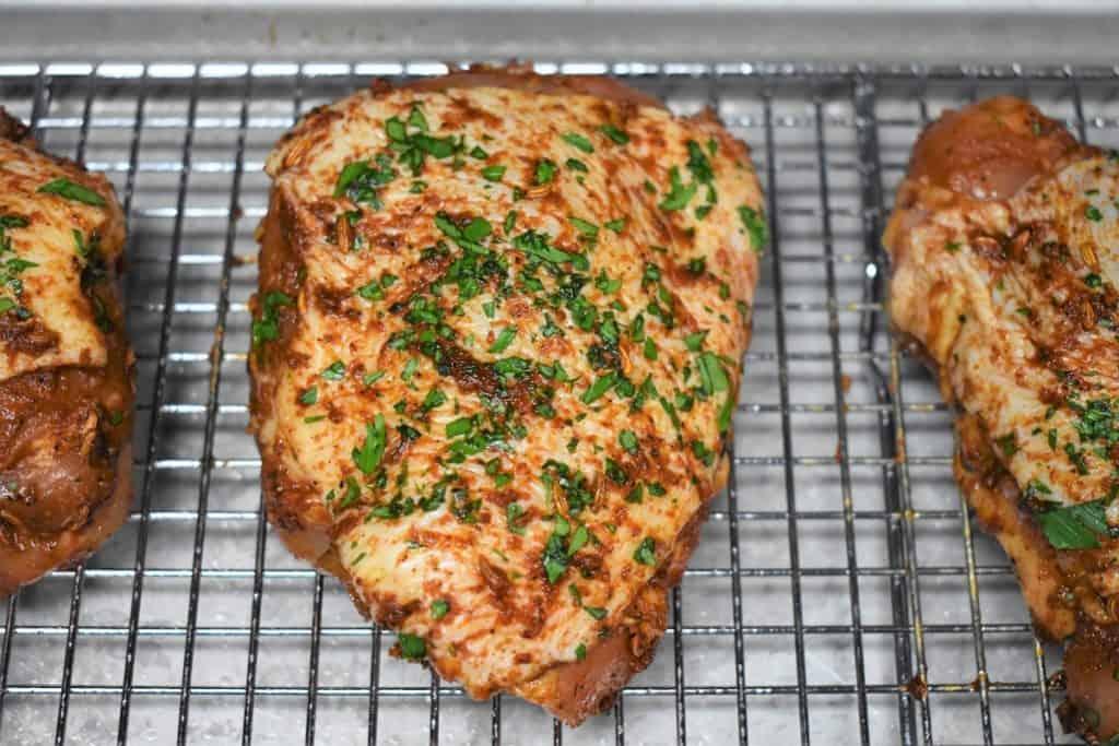 A raw seasoned chicken thigh on a baking sheet.