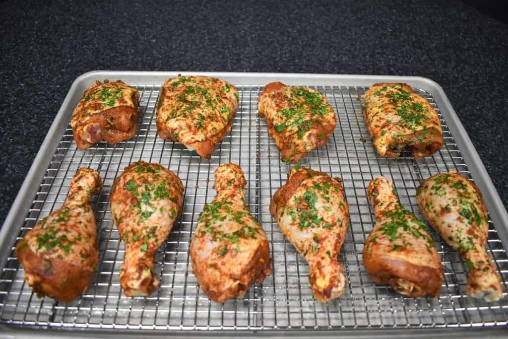 Ten pieces of seasoned raw chicken on Lined Baking Sheet