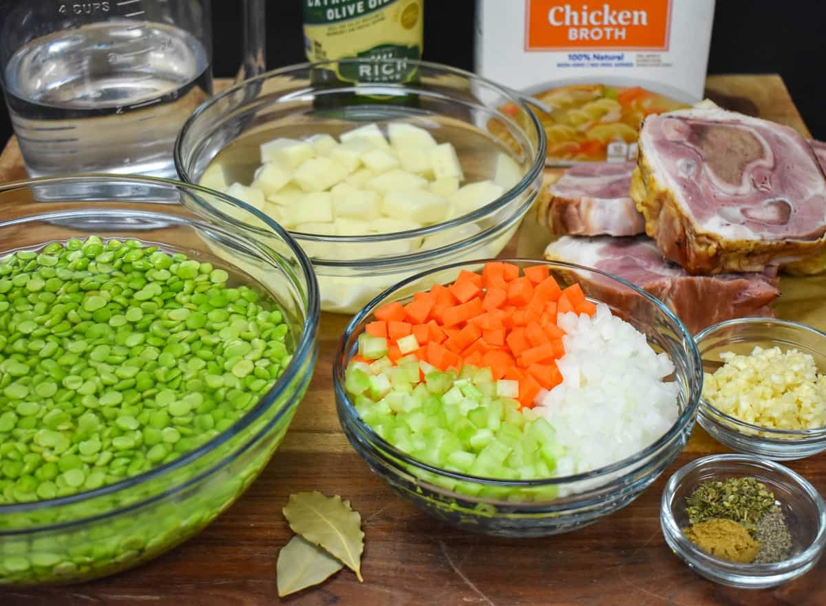 The prepped ingredients for the soup separated in glass bowls and displayed on a wood cutting board.