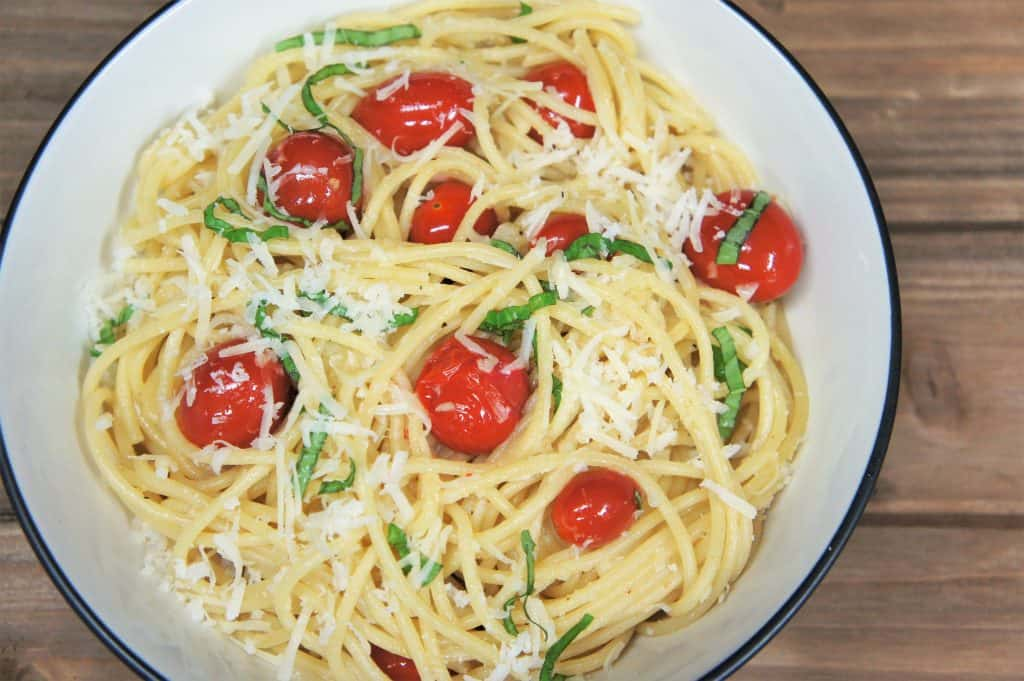 Spaghetti Aglio e Olio with Fresh Tomatoes and Basil served in a white bowl.