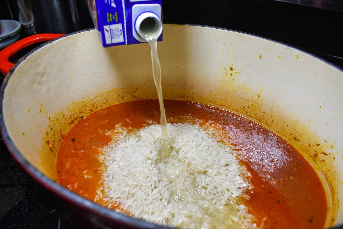 Chicken broth being added to white rice in a large pot.