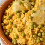 A close up of yellow rice and two chicken pieces garnished with sweet peas and served in a terracotta bowl.