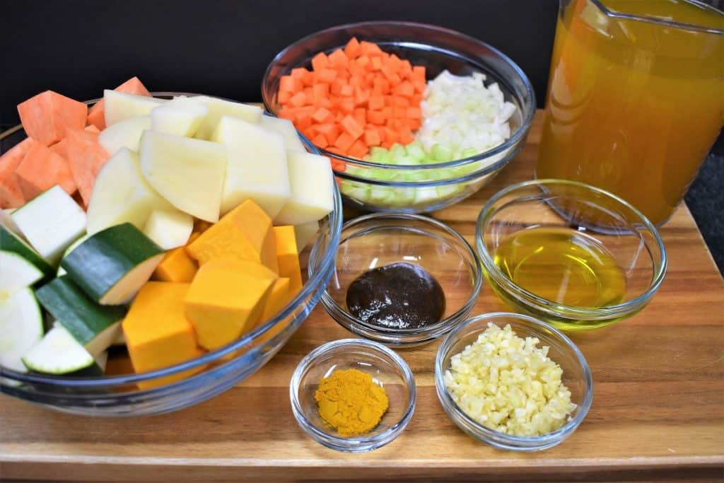 The ingredients for the creamy vegetable soup displayed on a wood cutting board.