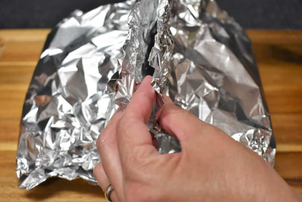 Crimping the top of a foil packet to seal.