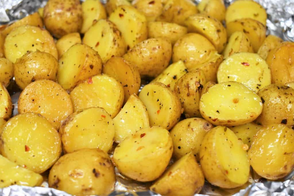 A close up picture of grilled potatoes in an open foil pack.