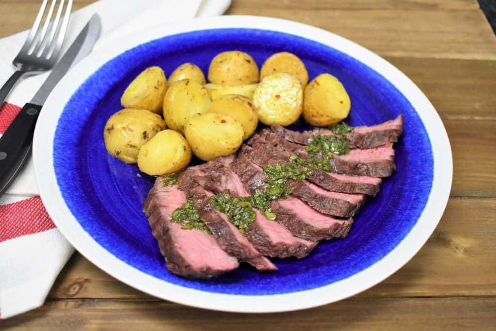 Grilled potatoes with sliced flat iron steak topped with chimichurri and served on a blue plate with a white rim.