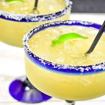 A margarita in a clear glass with a salted rim.