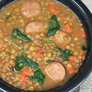 Lentil Sausage Soup served in a dark gray bowl.