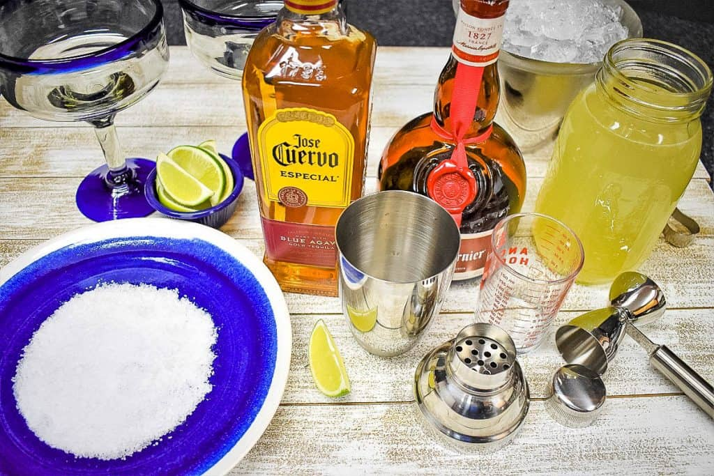 Ingredients for a homemade margarita displayed on a white wood board.