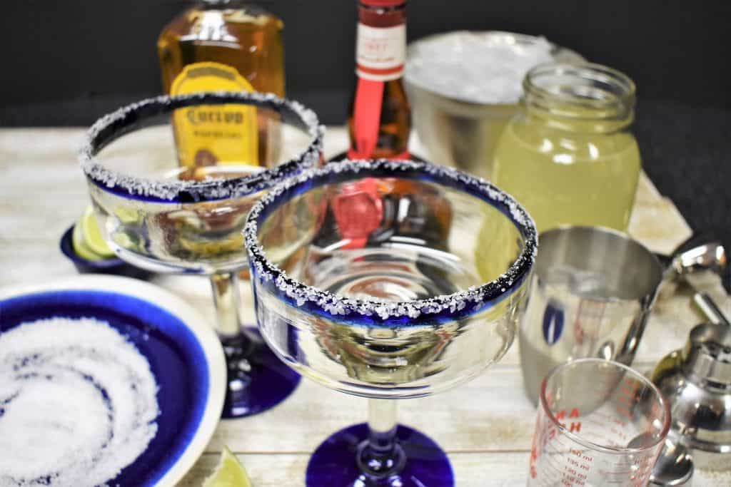 Ingredients for a margarita displayed, with an empty margarita glass with a salt rim in the front.