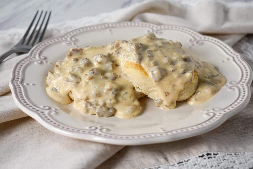 Sausage gravy served over biscuits on a white plate.