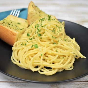 Spaghetti Aglio e Olio served on a black plate with two pieces of garlic toast in the background.