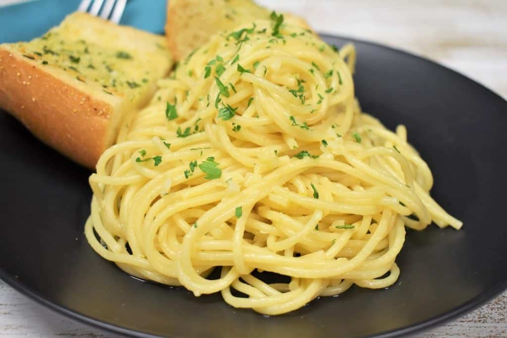 A close up of spaghetti aglio e olio served on a black plate of two pieces of garlic toast in the background.