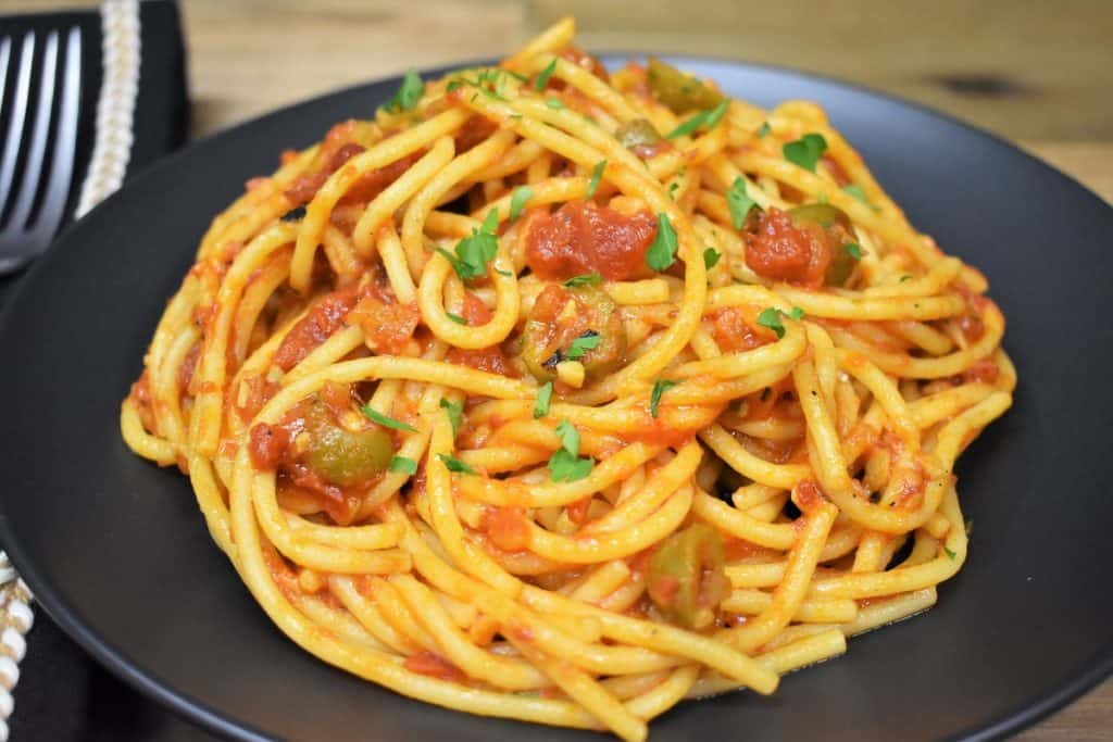 Spaghetti and a tomato olive sauce served on a black plate.