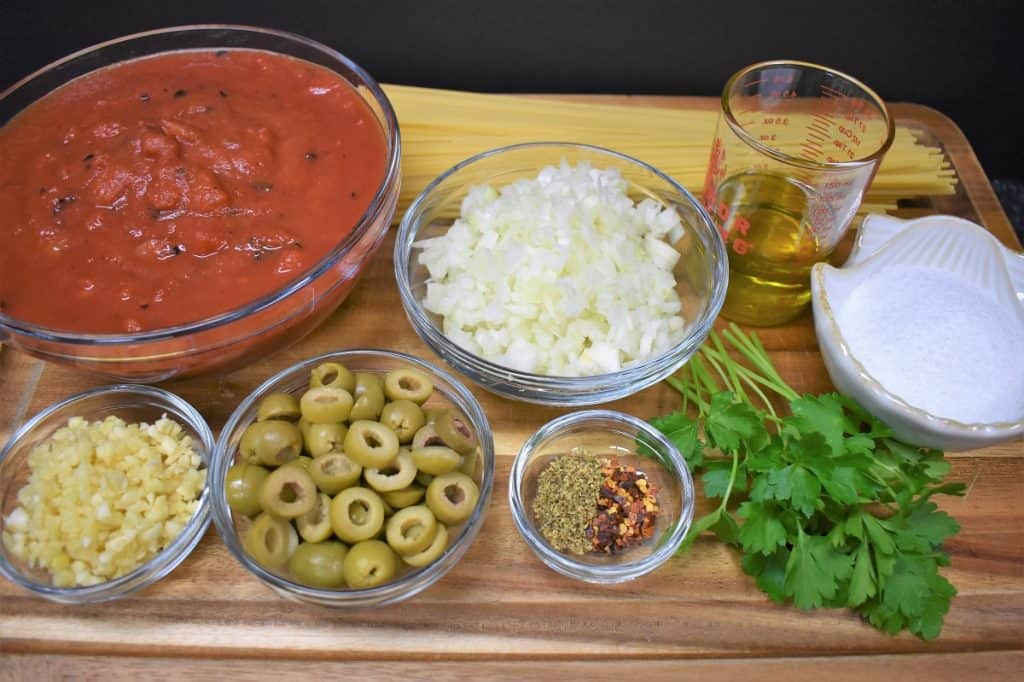 The ingredients of tomato and olive pasta displayed on a wood cutting board.
