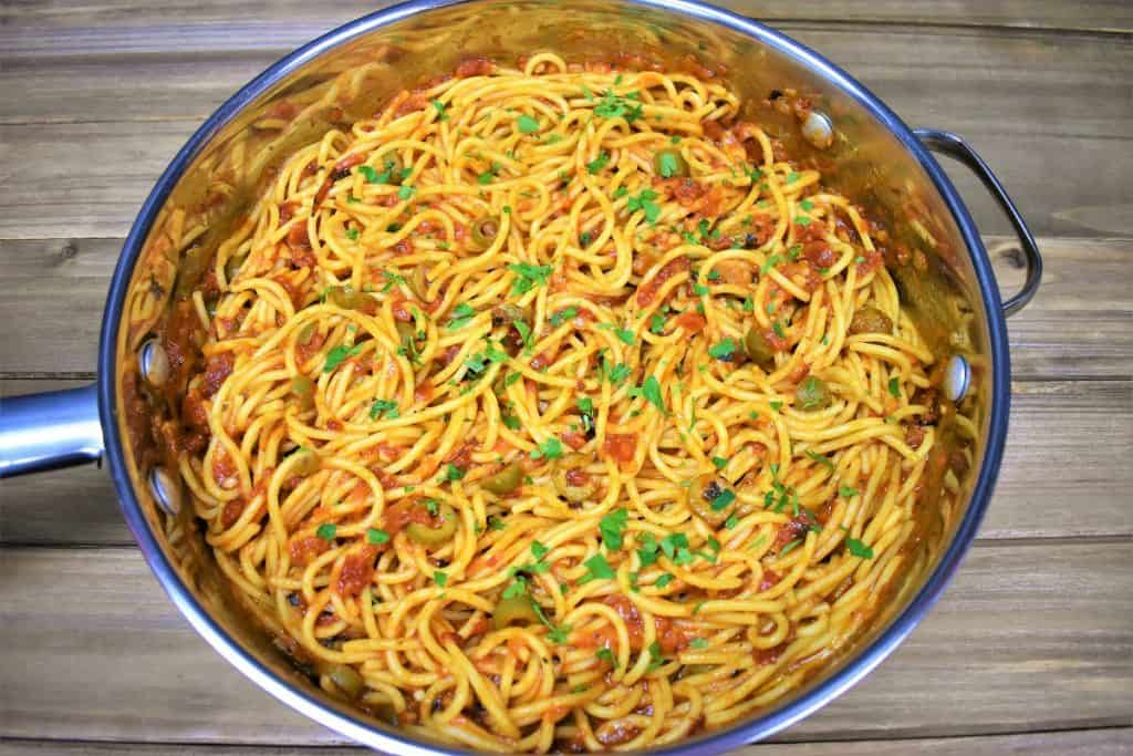 Spaghetti and tomato and olive sauce in a large skillet.