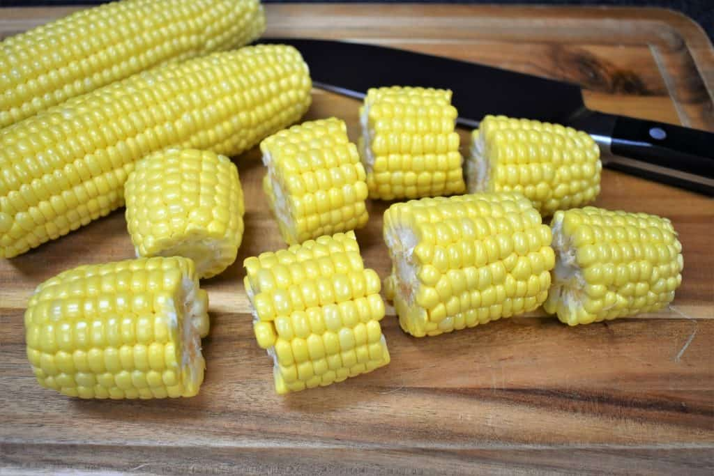 Fresh corn cobs cut into four pieces, displayed on a wood cutting board.