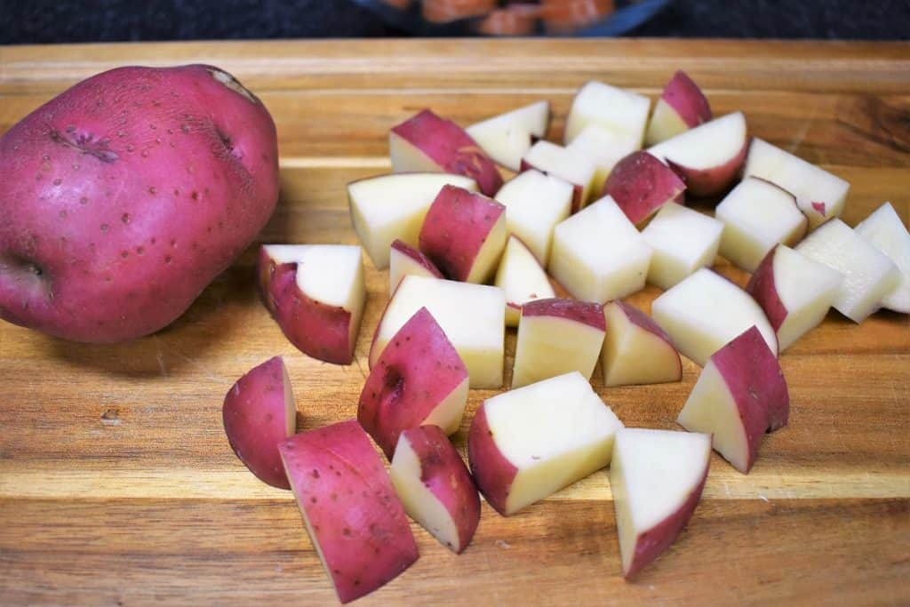 Diced Red Potatoes displayed on a wood cutting board.