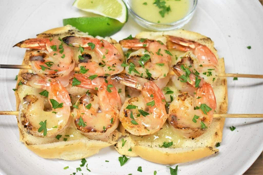 Two grilled shrimp skewers and butter lime sauce served on toasted bread on a white plate and garnished with parsley.