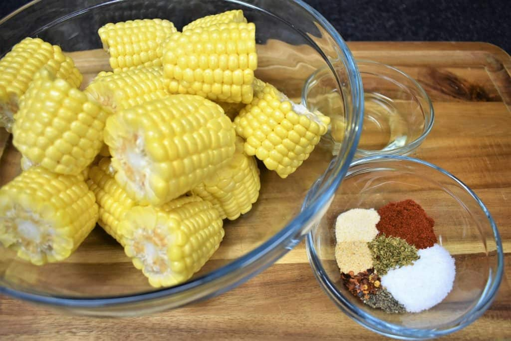 Cut corncobs in a glass bowl and a small bowl of seasoning displayed on a wood cutting board.