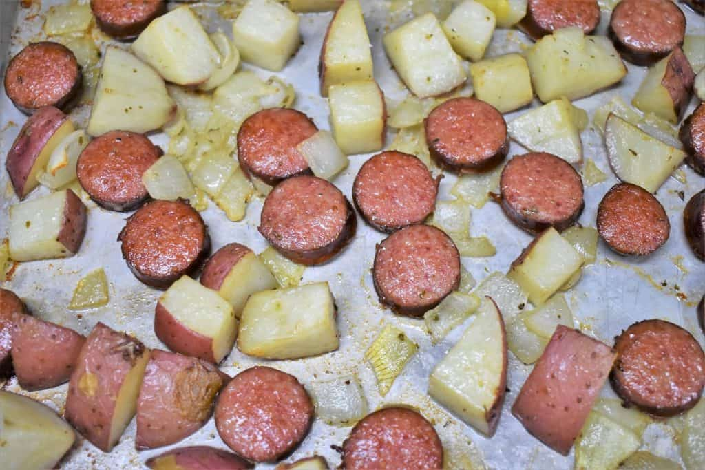 Baked sliced sausage and diced red potatoes arranged on a large baking sheet..