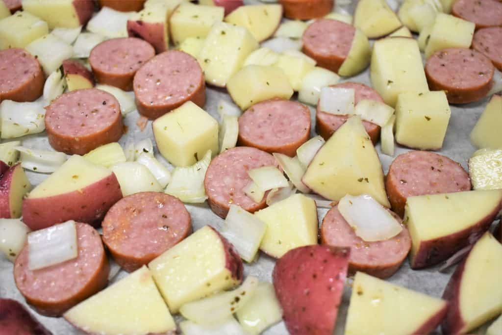 Sliced sausage, diced red potatoes and diced onions arranged on a large baking sheet, prior to baking.