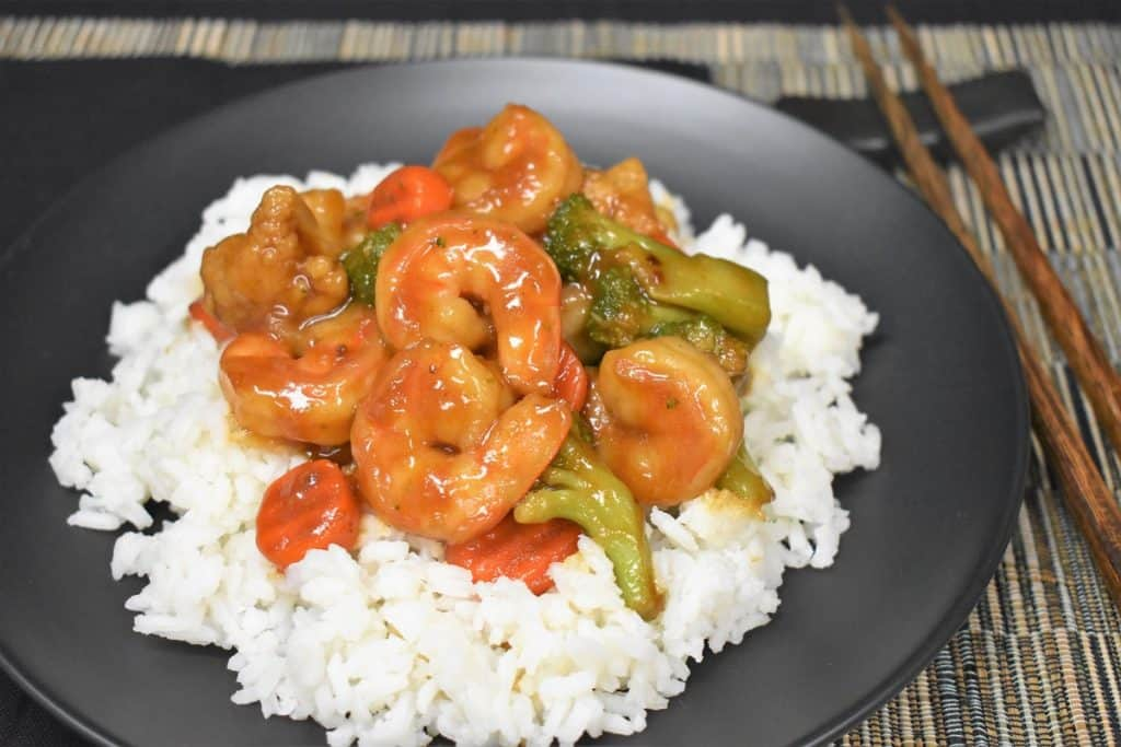 Shrimp and mixed vegetable stir fry served on a bed of white rice on a black plate.