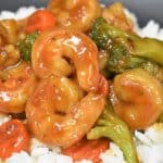 A close up image of shrimp and vegetable stir fry on a bed of white rice.