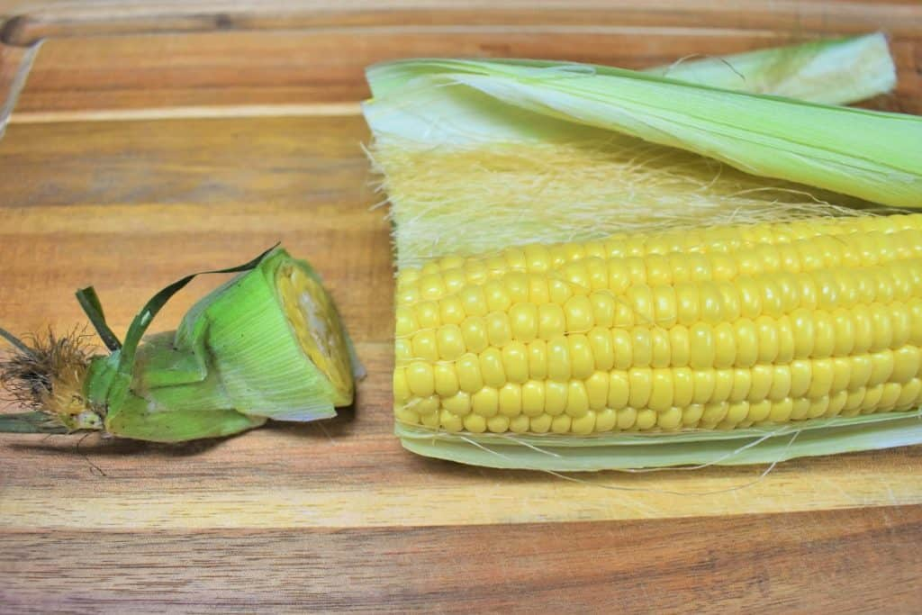 A fresh corn cob with half the husk removed, displayed on a wood cutting board.