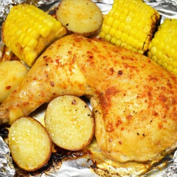 An open foil pack with a quarter chicken, corncobs and potatoes cut in half.