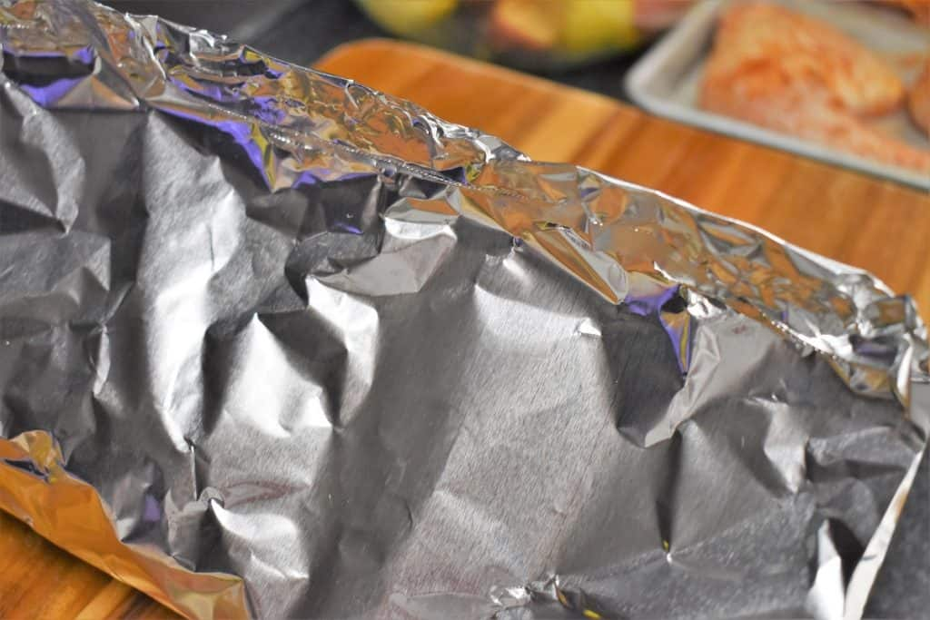 An aluminum foil pack being made, the top of the foil crimped together.
