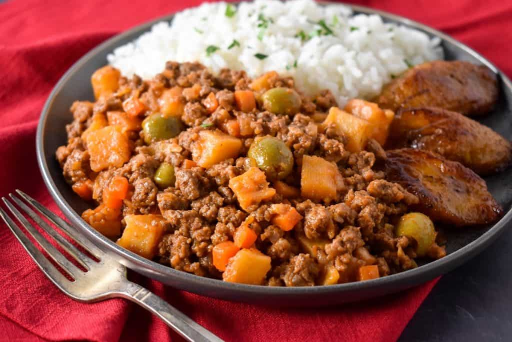The picadillo served with white rice and fried sweet plantains on a gray plate on top of a red linen.