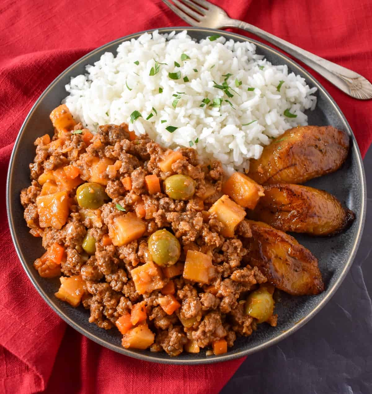 Close up image of the finished picadillo served with white rice and fried sweet plantains on a gray plate.