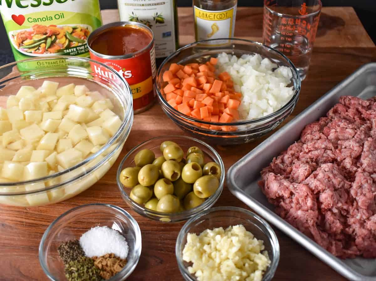 The prepped ingredients for the picadillo arranged on a wood cutting board.