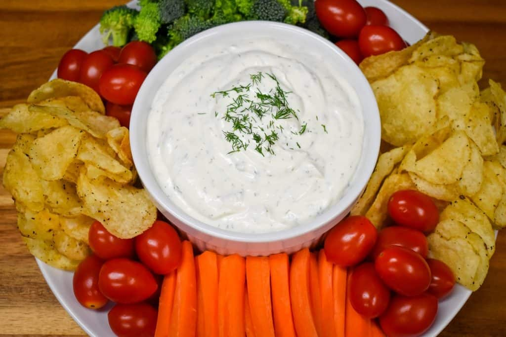 A top picture of dill dip served in a large white bowl with chips, grape tomatoes, carrots and broccoli florets arranged around the bowl.