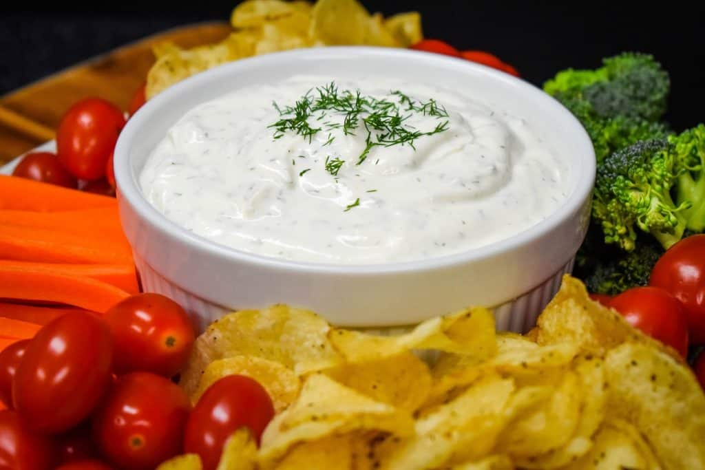 Dill dip served in a large white bowl with chips, grape tomatoes, carrots and broccoli florets arranged around the bowl.