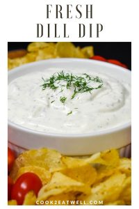 Dill dip served in a white bowl, garnished with chopped dill and surrounded by chips and grape tomatoes.