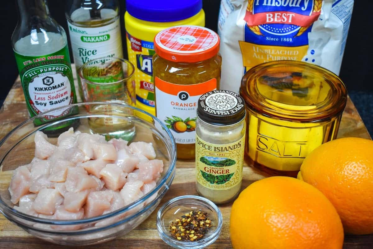 The ingredients for the orange chicken displayed on a wood cutting board.