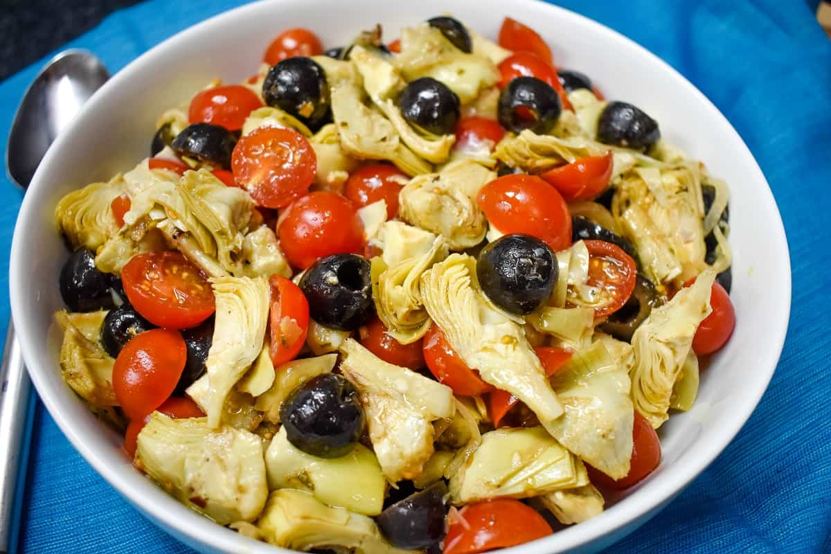 A cold salad with quartered artichokes, grape tomatoes, black olives and sliced onions tossed with an oil and vinegar dressing and served in a large white bowl on a blue cloth.