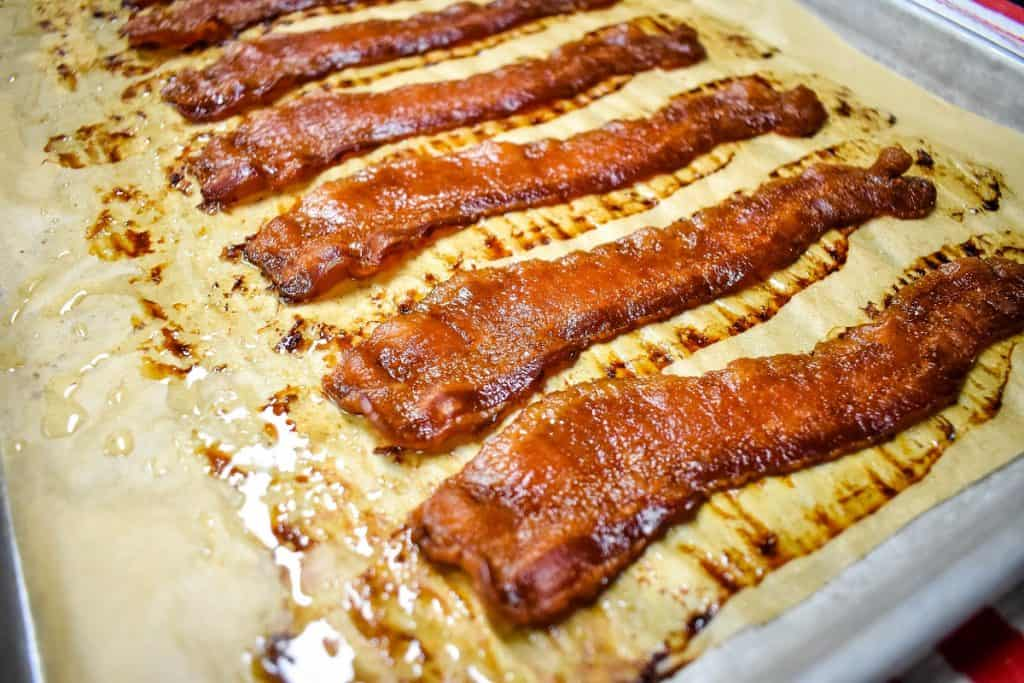 Cooked bacon on a baking sheet lined with brown parchment paper.