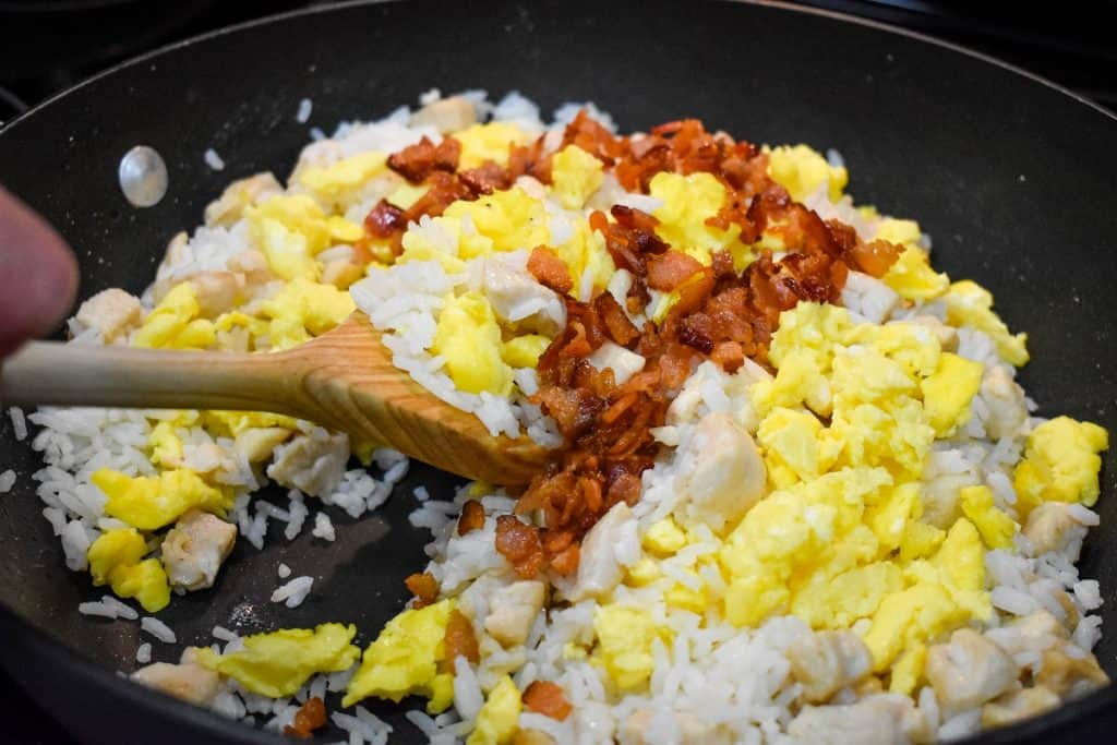 Chicken cubes, white rice, bacon bits and scrambled eggs being stirred in a large, black skillet.