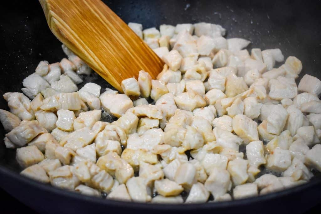 cooked small chicken cubes in a large, black skillet.