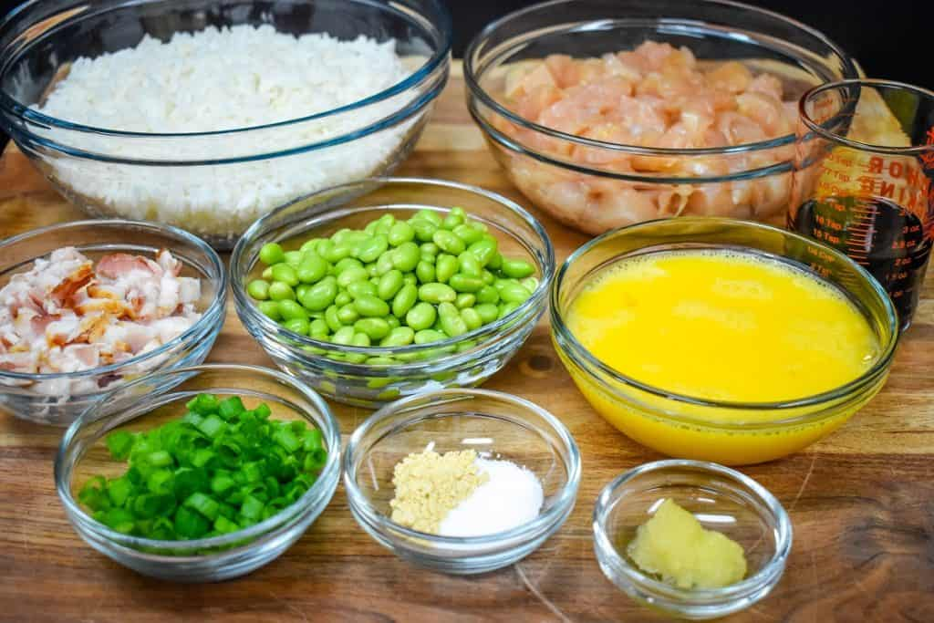 The ingredients for the chicken fried rice separated in clear glass bowls and displayed on a wood cutting board.