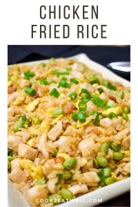 Chicken fried rice garnished with sliced green onions and served on a large platter.