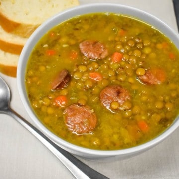 Lentils with andouille sausage soup served in a light gray bowl with bread slices in the background.