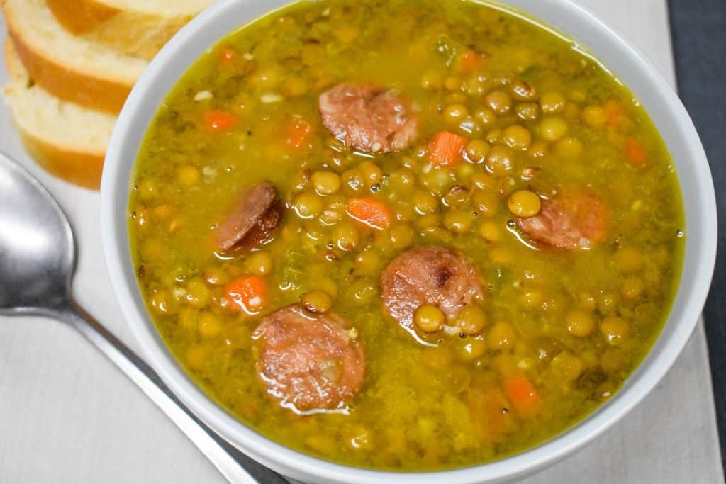 A close up picture of lentil and andouille sausage soup served in a light gray bowl.