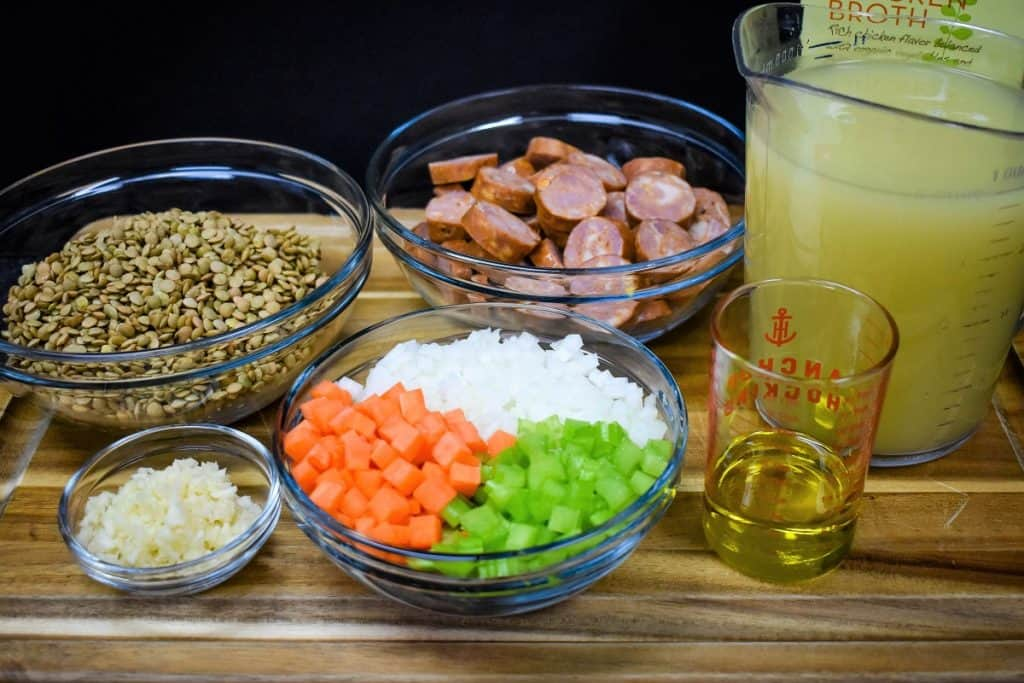 The ingredients for the lentil andouille sausage soup prior to cooking, arranged in clear glass bowls on a wood cutting board.