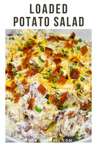 A close up image of loaded potato salad garnished with chopped bacon, shredded cheese and chopped chives.