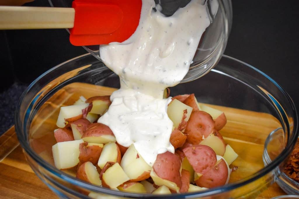 Mayonnaise and sour cream dressing being poured over cut red potatoes in a large, clear bowl.