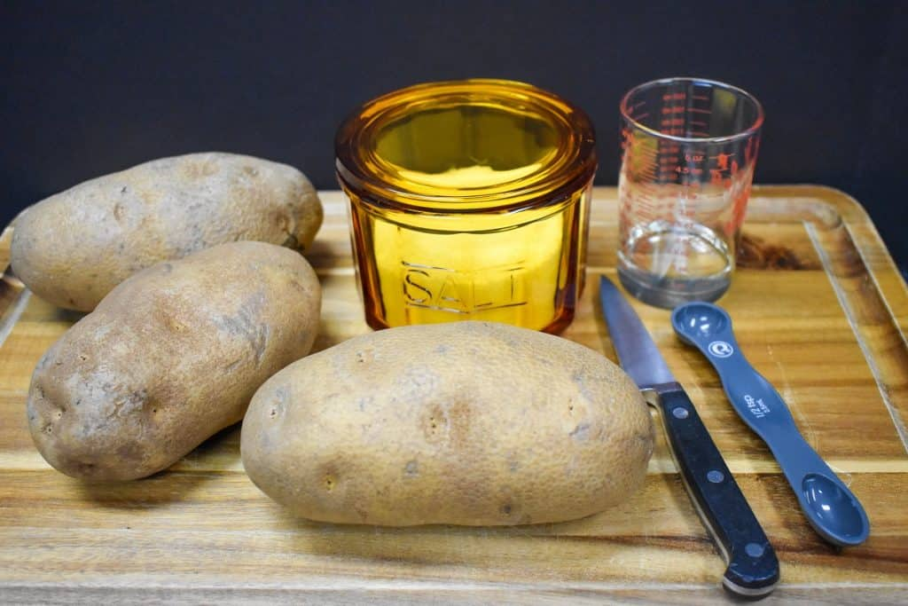 Three large russet potatoes, a salt cellar, oil and a paring knife displayed on a wood cutting board.